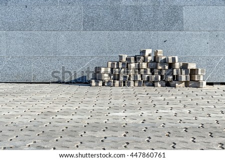 The sidewalk blocks which are accurately put near a granite wall - stock photo