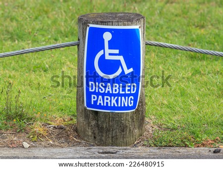 The sign of disabled parking on the street side, useful for supporting disability person. - stock photo