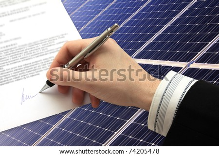 The Signature of Business Contract in front of the Solar Power Station - stock photo
