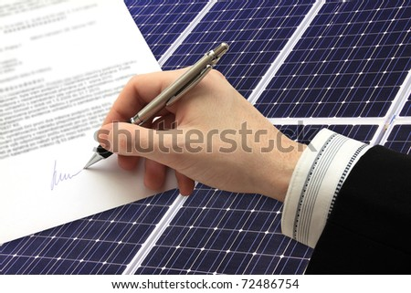 The Signature of Business Contract in front of the Solar Power Station in the green Nature - stock photo