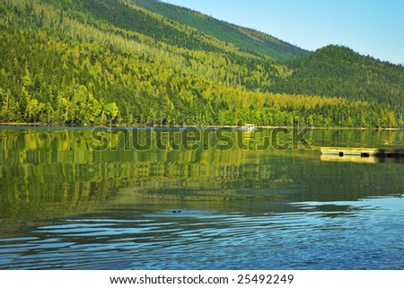 The silent lake surrounded by a wood, popular in fishermen, and a boat mooring - stock photo