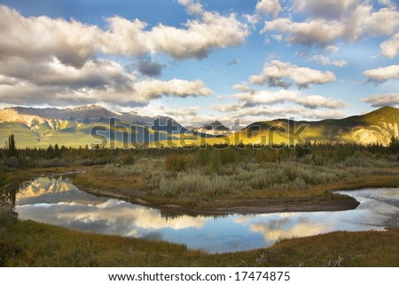 The silent river surrounded by fur-trees and bushes in the autumn. More magnificent pictures from the American and Canadian National parks you can look hundreds in my portfolio. Welcome! - stock photo