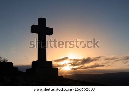 The silhouette of a cross shaped grave stone in a cemetery.