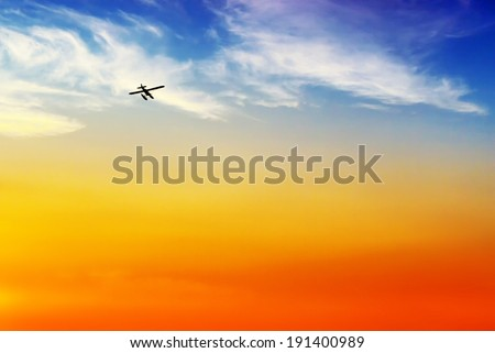 The silhouette of a float or pontoon plane flies off into the sunset.  A simple minimalist background image.    - stock photo