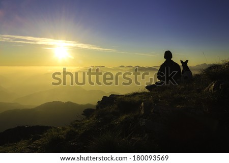 The silhouette of a man and his dog sitting on the top of a mountain watching a sunset together. Italy./ Man and his Dog - stock photo