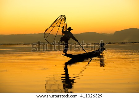 The silhouette of a man fishing from Burma. - stock photo