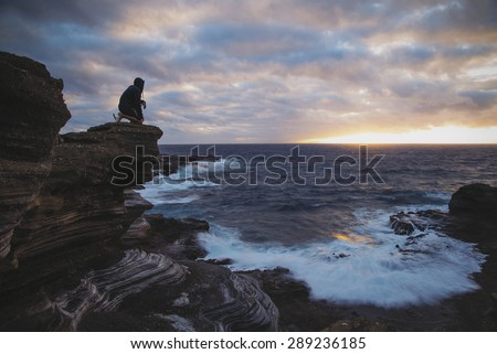The silhouette of a man kneeling on a ledge looking out to sea as the sun peaks up over the horizon.  - stock photo