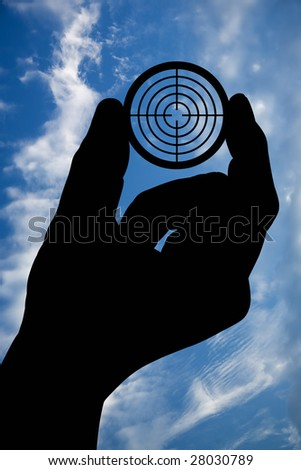The silhouette of a man's hand holds a target on a background of the sky with clouds. With clipping path. - stock photo