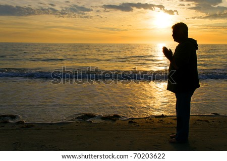 The silhouette of a man standing on the beach praying with a golden sunset behind him. - stock photo