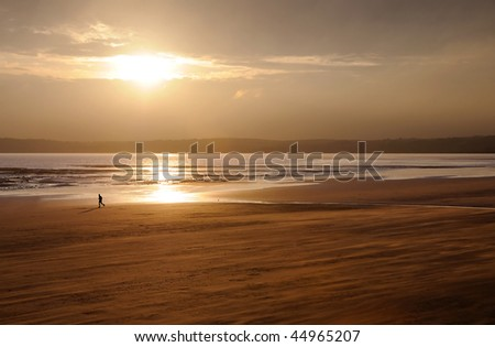 The silhouette of a person running on an otherwise deserted beach. the wind blows the sand in streaks across the beach. - stock photo