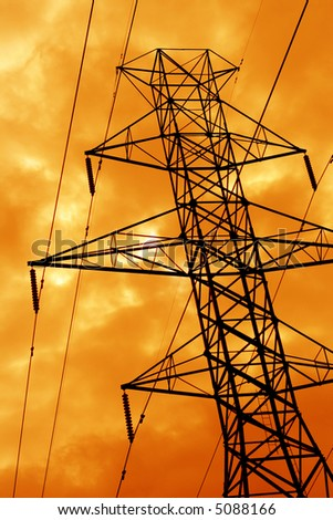 The silhouette of a power line tower against an ominous orange sky. - stock photo