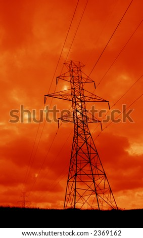 The silhouette of a power lines and towers against an ominous orange sky. - stock photo