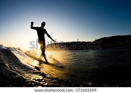 The silhouette of a surfer riding a wave at an empty surf spot - stock photo