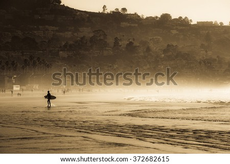 The silhouette of a surfer walking up the beach with his surfboard