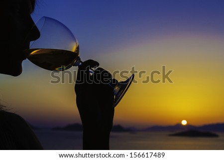The silhouette of a young woman drinking wine in a sunset over looking the Aegean Sea and islands, Turkey / silhouette of woman drinking wine at sunset - stock photo