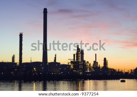 The silhouette of an oil refinery at sunset, against a radiant sky - stock photo