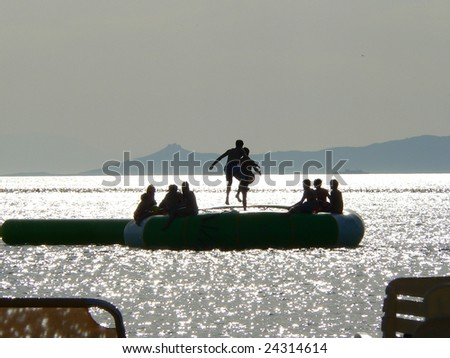 the silhouette of beach goers bouncing on a trampoline on the sea