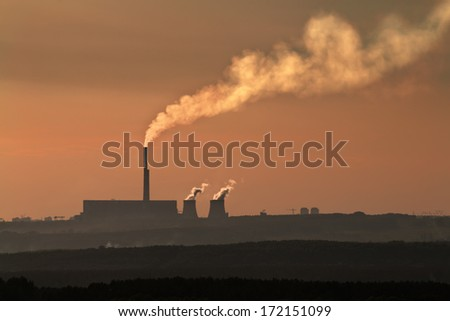 The silhouette of coal plant with thick smog around it - stock photo