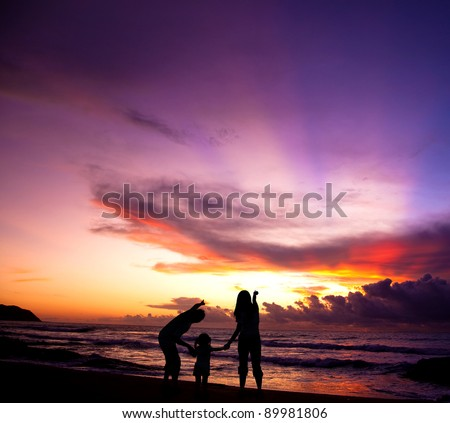 The silhouette of  family watching the sunrise on the beach - stock photo