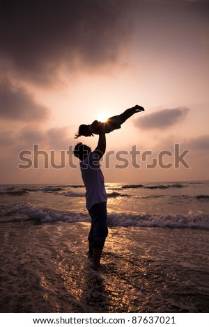 the silhouette of happy family on the beach - stock photo