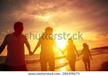 The silhouette of happy family walking on the beach - stock photo