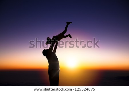 The silhouette of happy father and little girl with sunrise background - stock photo
