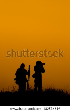 The silhouette of photographer take a photo at the cliff - stock photo
