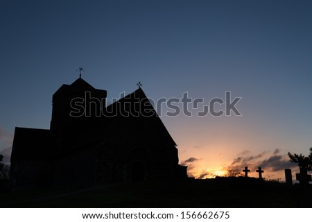 The silhouette of St Martha's on the Hill in Surrey at dawn.  Clear blue sky with some clouds where the sun is. - stock photo