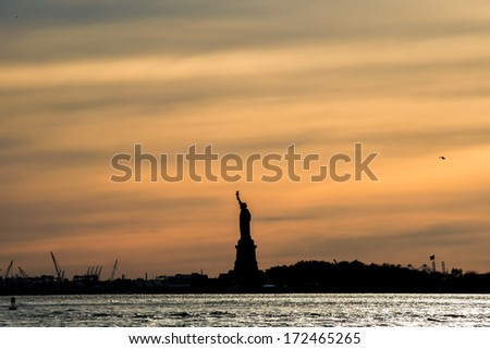 The silhouette of Statue of Liberty in New York City at sunset - stock photo