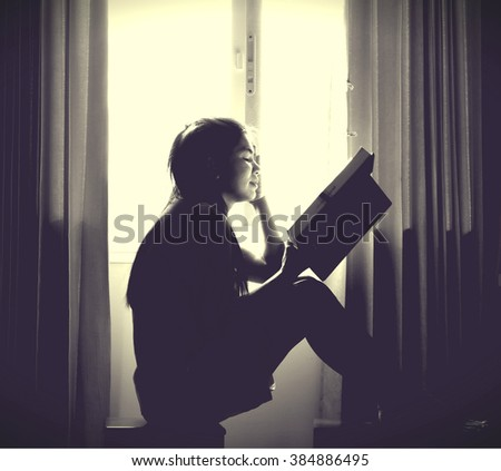 The silhouette of stressed and depressed woman worried with the black vignette on the corner and cream tone light on the center , out of focus - stock photo