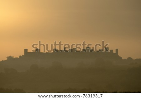The silhouette of the Castle of Monteriggioni in a golden sunrise (Italy)