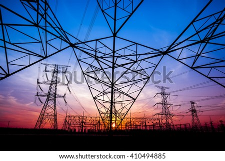The silhouette of the evening electricity transmission pylon - stock photo