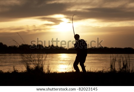 The silhouette of the guy with a fishing tackle, at sunset, which fishes - stock photo