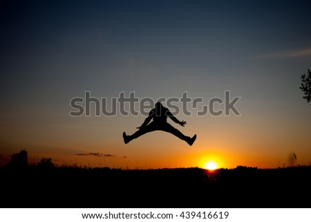 The silhouette of the man jumping with sunset background,concept of happiness, joy, joyful life