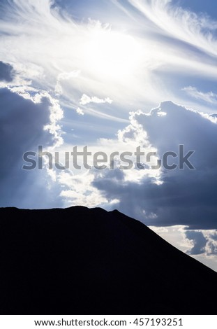 The silhouette of the mountains in the background of the sun and beautiful clouds