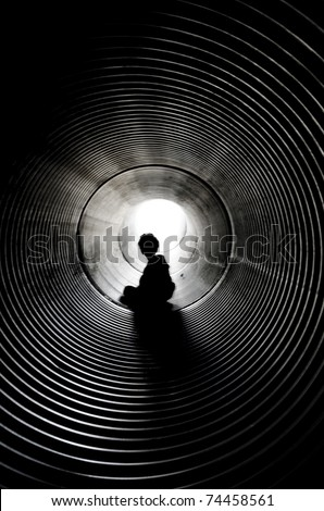 The silhouette of the sitting boy with light at the end of tunnel - stock photo