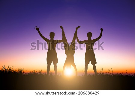 The Silhouette of young people catching a handstand person - stock photo