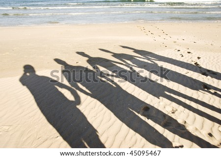 The silhouettes of five people on the beach - stock photo