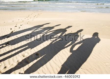 The silhouettes of five people on the beach in late afternoon sunlight - stock photo