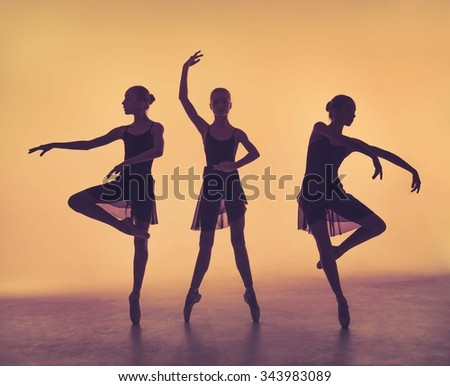 The silhouettes of young ballerinas posing on a gray background. - stock photo