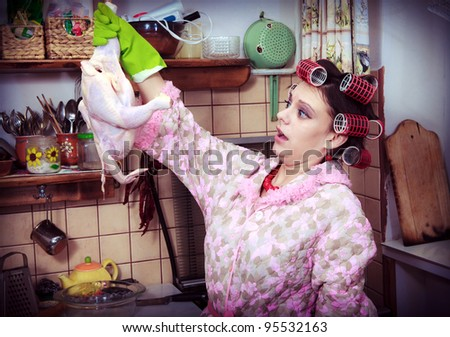 The silly housewife with carcass of a hen in hands - stock photo