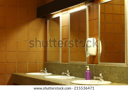 The sinks in a modern public rest room. - stock photo