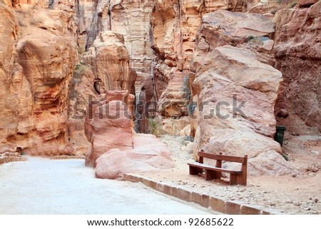 The Siq, the narrow slot-canyon that serves as the entrance passage to the hidden city of Petra, Jordan, seen here with tourists walking.This is an UNESCO World Heritage Site - stock photo