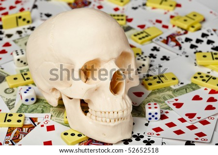 The skull on a background of playing cards, dominoes and money - stock photo