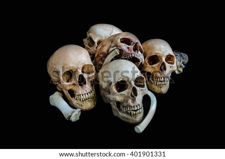 The skull under the candle light in the dark - stock photo