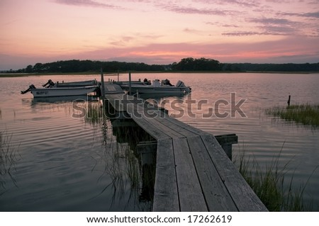 The sky clouds and water turn pink as the sun sets over a distressed old wooden dock and boats on the backwaters in Niantic Connecticut USA New England summer sunset at the beach with hints of yellow - stock photo