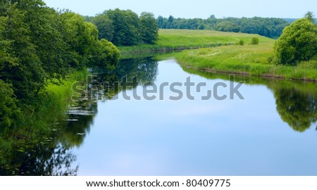 The sky is reflected in the river - stock photo
