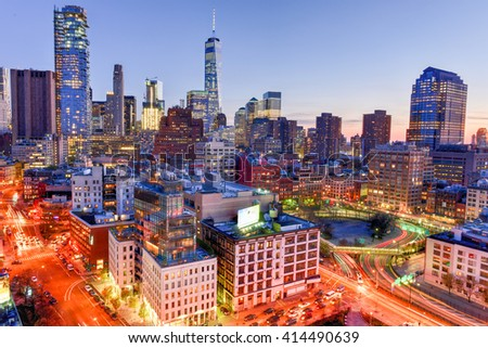 The skyline of downtown Manhattan, New York at sunset with trails of traffic in the street.