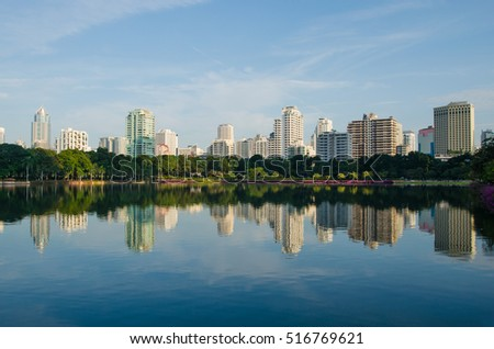 the skyline of metropolis building with the green park and blue sky background , the city park reflection from water in lake.