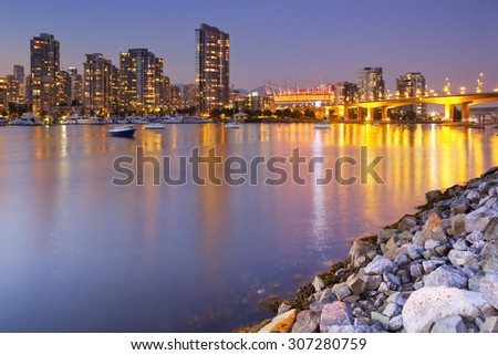 The skyline of Vancouver, British Columbia, Canada from across the water at dusk. - stock photo